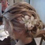 textured piecy twisted curls and two orchids create stunning bridal wedding hairstyle, up off the back of the neck, perfect look for a tropical, summer, beach wedding, very popular