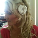 a single white rose pinned to the side of a half up half down wedding hairstyle with soft waves, blonde and very beautiful