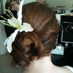 white lilly in bridemaids hairstyle, upstyle pinned to the side with pieces of hair looped through
