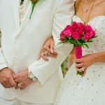bride and groom white suit hot pink roses diamonte wedding gown