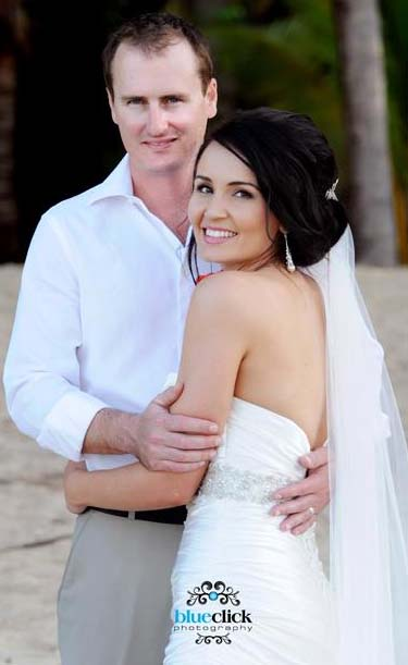 wedding at Kewarra Beach Resort, the bride and groom on the beach. white wedding dress, burnt orange theme, soft upstyle swept to the side with lots of height at the crown. loose curls down around the bride's face. flawless foundation, waterproof and smudge proof. smoky eyes in brown and orange, false lashes really makes this bridal makeup pop. stunning